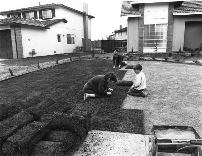 "Bill Owens, I bought the lawn in six-foot rolls. It's easy to handle. I prepare the ground and my wife and son helped roll out the grass. In one day you have a front yard. From the series ""Suburbia"", 1973. Gelatin-silver print, 7 x 9 inches. Image courtesy of the artist and Robert Koch Gallery. © Bill Owens"
