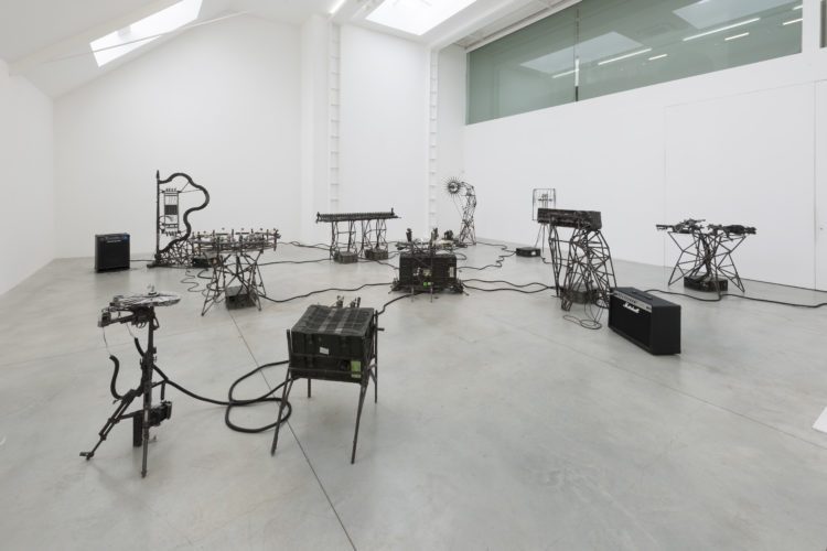 Art installation of speakers and other music instruments in a white room