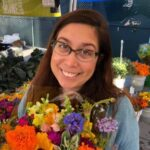 Woman smiling facing the camera while holding flowers