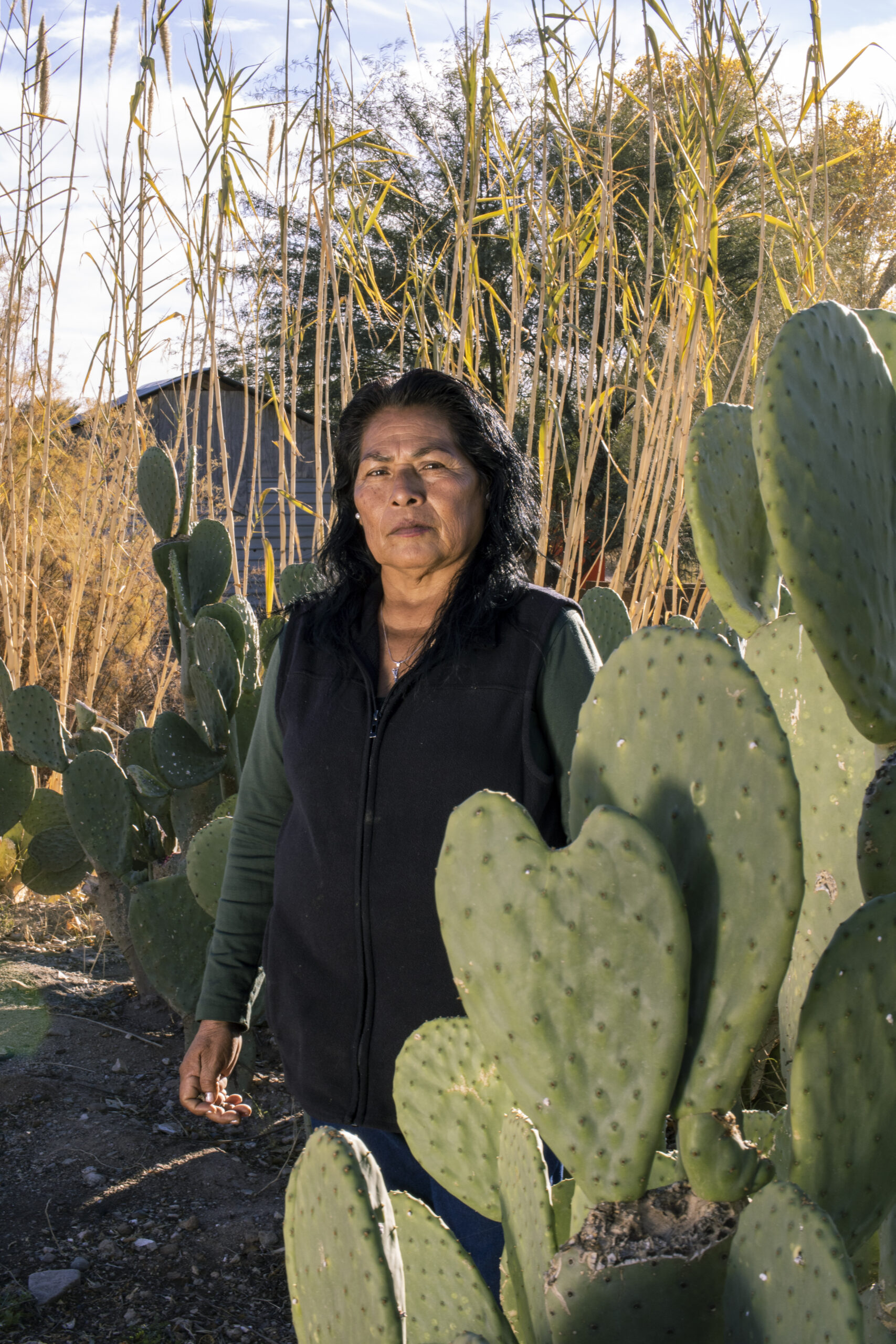 Woman facing the camera standing by a cactus.