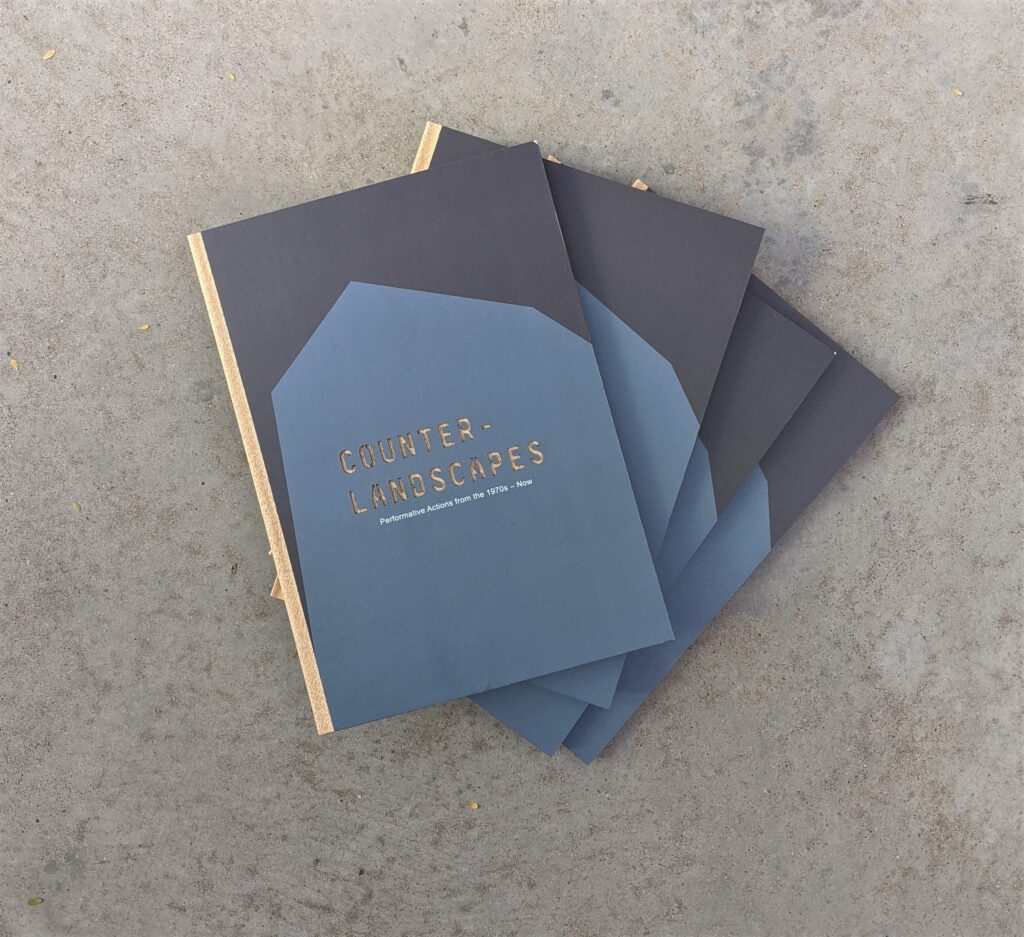 Flat lay of fanned out copies of Counter-Landscapes catalog on cement floor.
